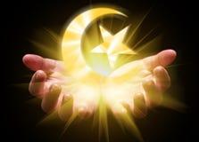 托起和拿着或者显示伊斯兰教的新月形月亮和星的手 免版税库存图片