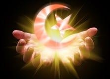 托起和拿着或者显示伊斯兰教的新月形月亮和星的手 库存照片