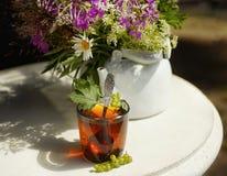 托起红茶白色水壶阳光桌花花束户外 免版税库存照片