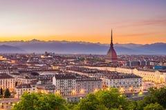 托里诺都灵,黄昏的意大利都市风景与五颜六色的喜怒无常的天空 痣耸立在下面有启发性城市的Antonelliana 图库摄影