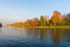 托里诺都灵-意大利的城市视图日落的在与教会的秋天季节俯视波河和五颜六色的树的小山顶的 Cle 库存照片