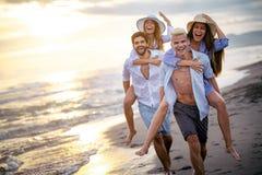 扛在肩上他们的女朋友的愉快的男朋友在海滩 库存照片
