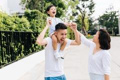 扛在肩上他的儿子的逗人喜爱的亚裔父亲与他的妻子一起在公园 举手的激动的家庭与幸福一起 免版税库存图片