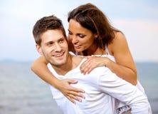 扛在肩上他的女朋友的愉快的年轻人 库存照片