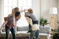 扛在肩上儿子和女儿,家庭playin的愉快的年轻父母 库存照片