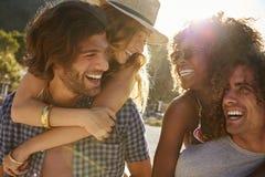 扛在肩上在海滩,伊维萨岛,西班牙的两对年轻夫妇 免版税库存图片