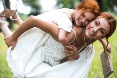 扛在肩上女儿的母亲在公园 库存照片