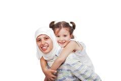 扛在肩上她的女儿的美丽的回教母亲 库存图片