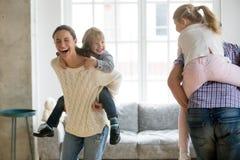 扛在肩上小儿子的愉快的妈妈在家使用与家庭 库存图片