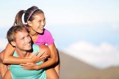 扛在肩上愉快的年轻的夫妇外面 免版税库存图片