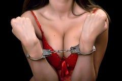 扣上手铐的红色女用贴身内衣裤的性感的妇女 免版税库存照片