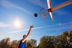 扣篮响声 做灌篮的年轻蓝球运动员侧视图  免版税图库摄影