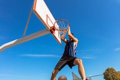 扣篮响声 做灌篮的年轻蓝球运动员侧视图  图库摄影