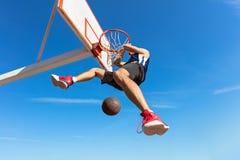 扣篮响声 做灌篮的年轻蓝球运动员侧视图  库存图片