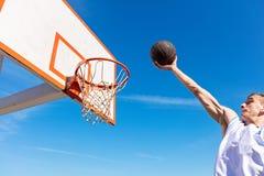 扣篮响声 做灌篮的年轻蓝球运动员侧视图  免版税库存图片