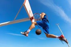 扣篮响声 做灌篮的年轻蓝球运动员侧视图  库存照片