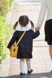 扣紧她的母亲` s手撤退形象的幼儿园制服的日本女孩 免版税图库摄影