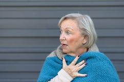 扣紧她的胸口的被震惊的年长妇女 免版税库存照片
