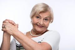 扣紧手的愉快的年长妇女 免版税图库摄影