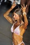 执行一个双重二头肌姿势的女性兢争者 免版税库存照片