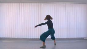 执行一个情感舞蹈的年轻俏丽的灵活的女性行动射击在空的屋子户内在舱内甲板 股票视频