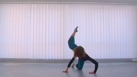 执行一个情感舞蹈的年轻美丽的灵活的女性行动射击在空的屋子户内在舱内甲板 股票录像