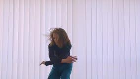 执行一个情感舞蹈的年轻逗人喜爱的灵活的女性行动射击在空的屋子户内在舱内甲板 股票视频
