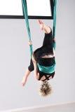 执行一个空中瑜伽翻筋斗的妇女 免版税库存图片