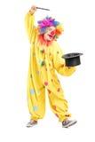 执行一个魔术技巧的马戏团小丑的全长纵向 免版税库存照片