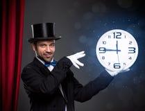 执行一个魔术技巧的魔术师与时钟 库存照片