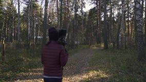执行三脚架在金黄小时和走在森林公路附近的美丽的小姐在autmn 股票录像