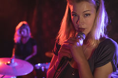 执行与女性鼓手的歌手画象在夜总会 库存图片