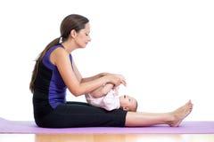 执行与她的婴孩的母亲瑜伽执行 免版税库存照片