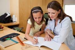 执行与她的母亲的女孩家庭作业 库存图片