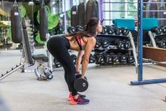 执行举重deadlift锻炼的适合的妇女与哑铃在健身房 免版税库存照片