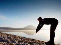 执行人的海滩 行使和舒展在湖的活跃人剪影 免版税库存图片