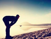 执行人的海滩 行使和舒展在湖的活跃人剪影 免版税图库摄影