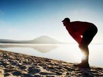 执行人的海滩 行使和舒展在湖的活跃人剪影 库存照片