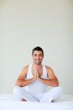 执行他的人瑜伽年轻人的卧室 免版税库存照片