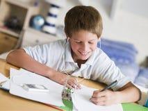 执行他的家庭作业年轻人的男孩 免版税库存照片