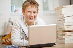 执行他的家庭作业的男孩少年 免版税库存图片