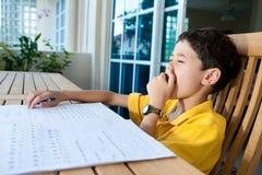 执行他的家庭作业的男孩打呵欠 免版税库存照片