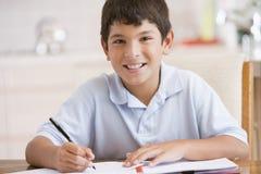 执行他的家庭作业的男孩 库存图片
