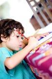 执行他的家庭作业的男孩 免版税图库摄影