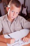 执行他的家庭作业的男小学生 免版税库存照片