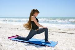 执行低刺女子瑜伽的海滩 免版税库存照片