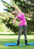 执行体育运动的妇女舒展执行 免版税库存图片