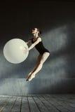 执行使用白色气球的灵活的吸引人体操运动员 免版税库存照片