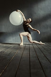 执行使用白色气球的熟练的年轻体操运动员 免版税库存图片