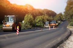 执行修理工作:涂柏油堆积和按沥青的热的位置路辗 修理路的机器 免版税图库摄影
